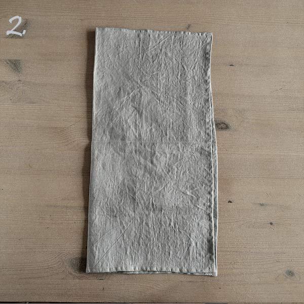 Trin 2 - fold servietten over midten på langs