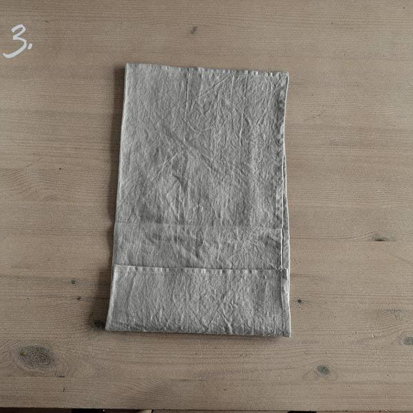 Trin 3 - fold den nederste del af servietten op ca 1/4 af serviettens længde.