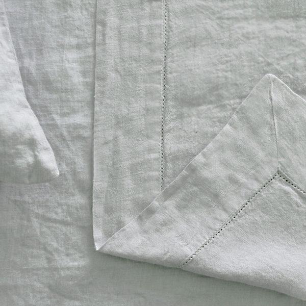 grå hør sengetæppe med hulsøm og påsyet bort
